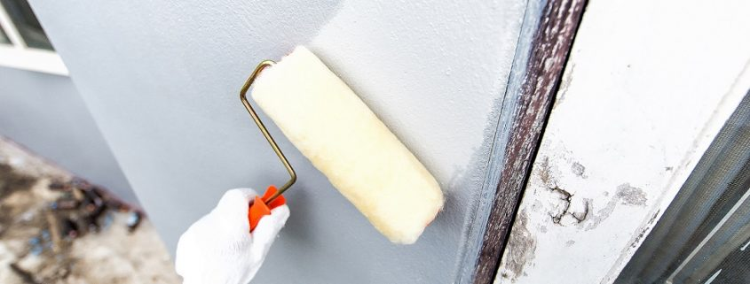 white Concrete paint being applied on a wall with a roller