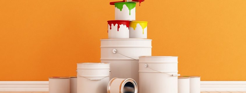 orange decorative coating on interior wall with paint cans