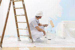 man applying blue interior wall paint
