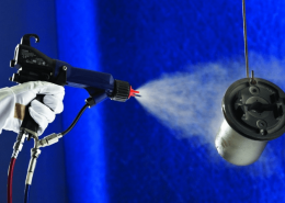 spraying a metal piece using industrial coating equipment